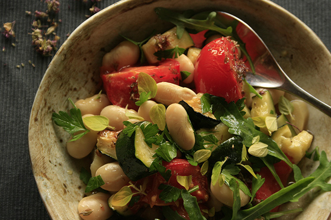 Butter beans with baked tomatoes garlic and courgettes in a bowl