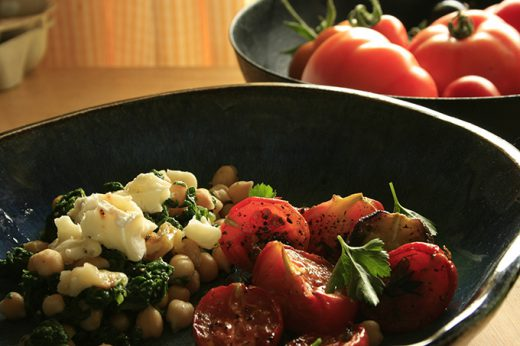 chickpea and spinach and roasted tomato salad in a bowl