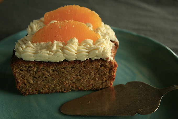 carrot cake on a plate with marscapone and orange clices
