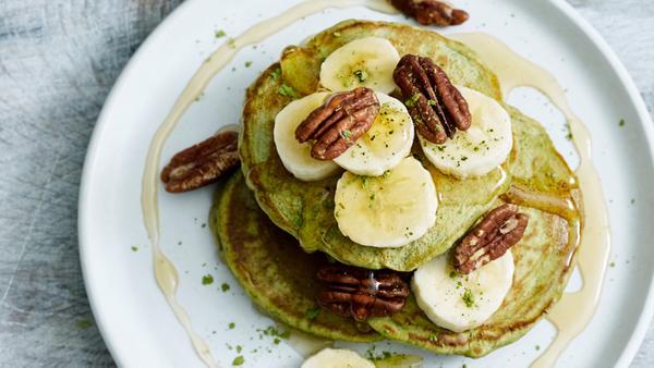 Matcha tea and medicinal mushroom pancake stack with bananas and pecan nuts