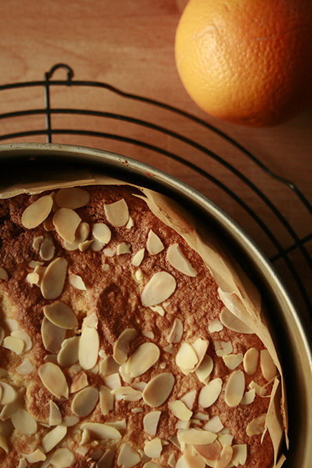 orange and almond cake in a tin sprinkled with flaked almonds