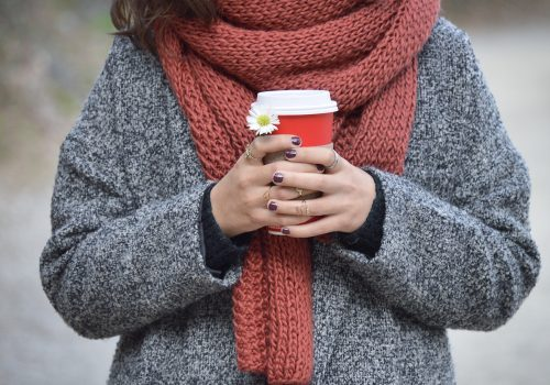 Woman wearing a scarf holding a coffee cup