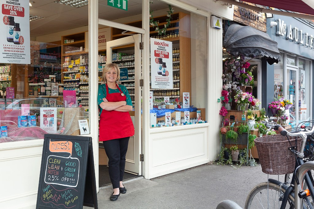 Image of Nourish female staff member standing in doorway of shop