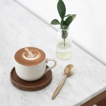 coffee on a table with a spoon and plant