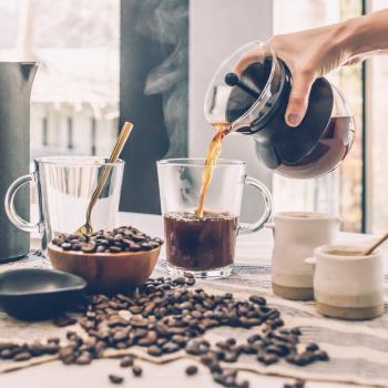 coffee being poured into a glass mug